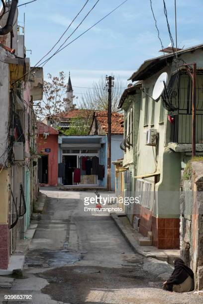 old city street with sitting woman and child and a minaret at the background. - emreturanphoto stock pictures, royalty-free photos & images