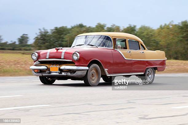 Old classic car drives by Cuban highway