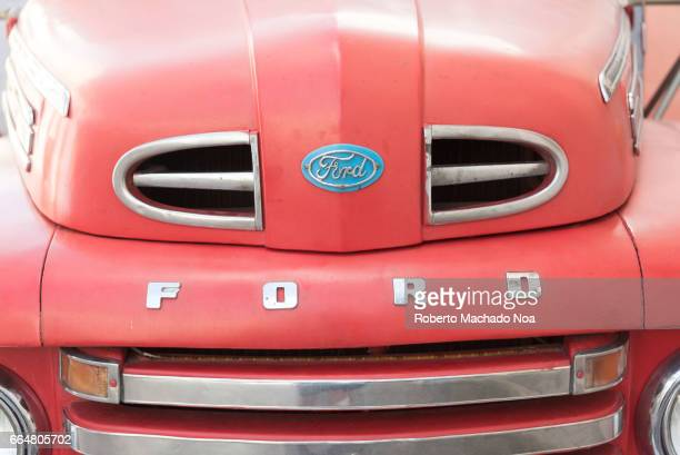 Old classic Ford truck sign logo in front of vehicle Working obsolete cars are typical of the Caribbean Island
