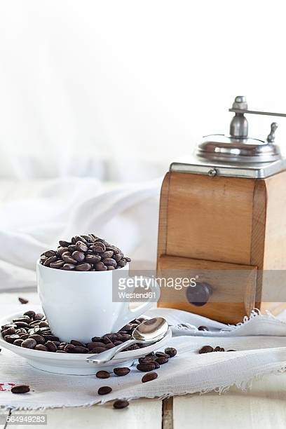 Old coffee mill and coffee cup filled with coffee beans