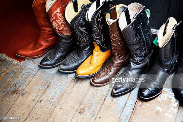Old colored cowboy boots in a wooden floor