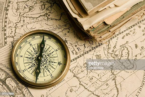 old compass over ancient map - cartography stock photos and pictures