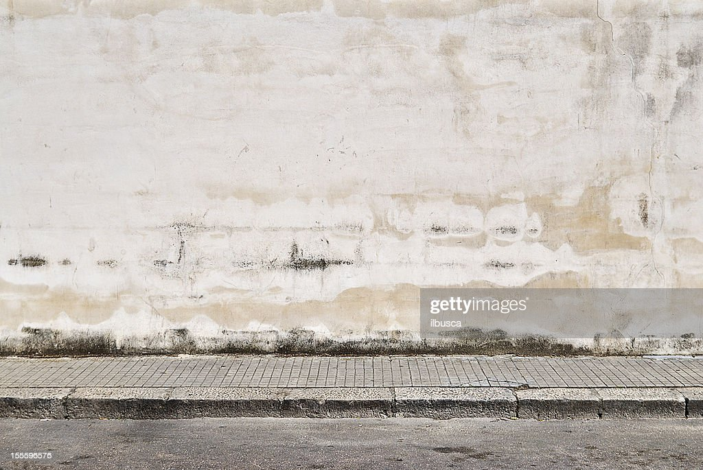 Old concrete grunge wall with sidewalk : Stock Photo