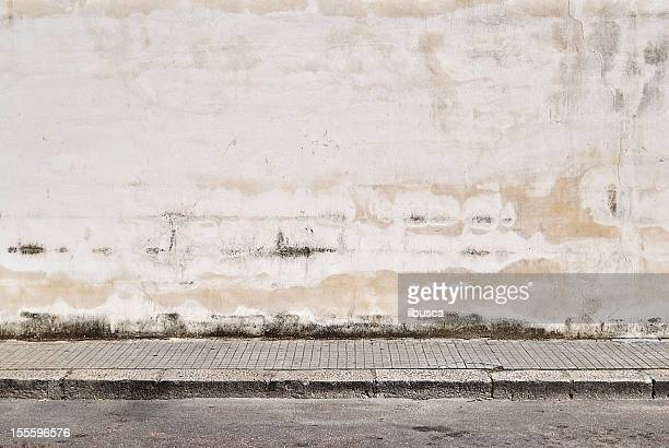 old concrete grunge wall with sidewalk - muur stockfoto's en -beelden