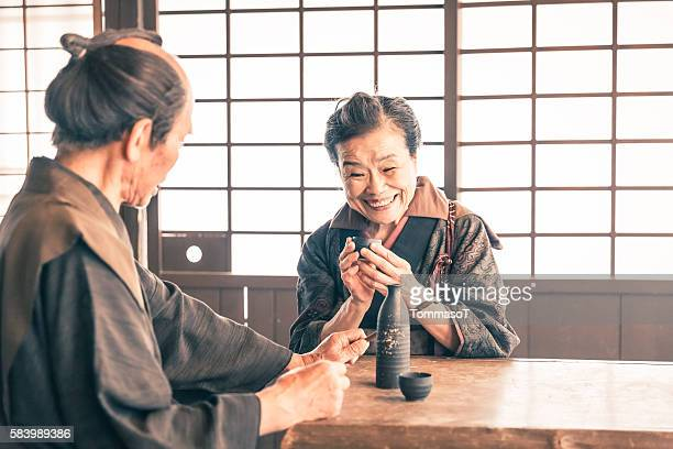 Old couple drinking sake in a traditional japanese house