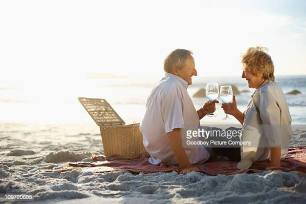 Old couple enjoying their vacation by toasting wine glasses