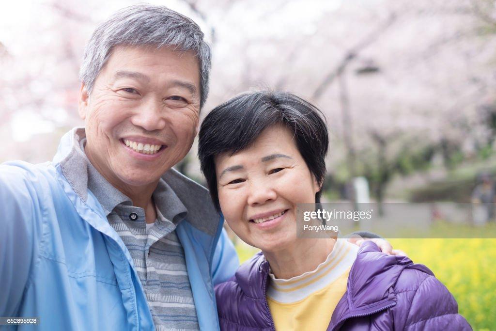 Gamla par är leende till dig : Bildbanksbilder