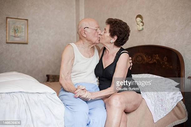 old couple kissing holding hands - kissing on the mouth stock photos and pictures