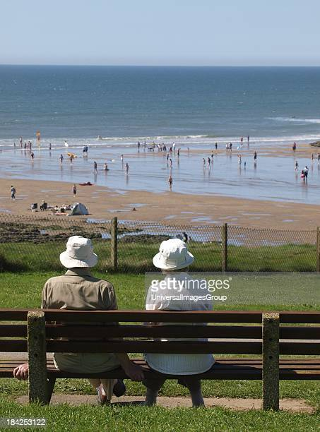 Old couple sat on park bench looking out to sea, Bude, Cornwall, UK.
