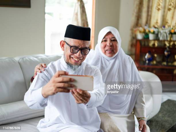 old couple selfie - hari raya celebration stock pictures, royalty-free photos & images