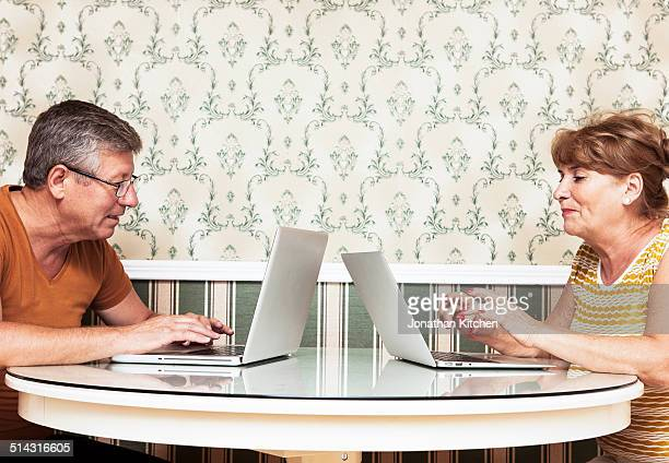 Old couple sit opposite each other with laptops
