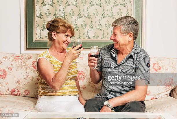 Old couple toast with wine glasses