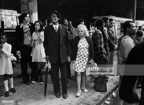 Old couple walking down the street holding hands Notting Hill Carnival London UK 1975