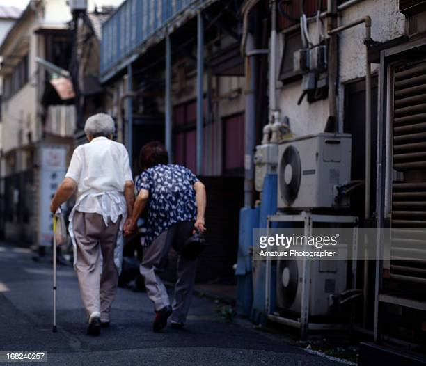 Old couple walking together holding hand.