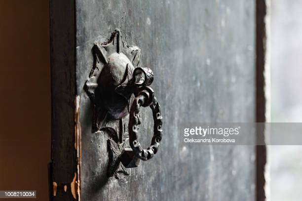 old courtyard door with an antique ornamental iron latch and knocker. - door knocker stock photos and pictures