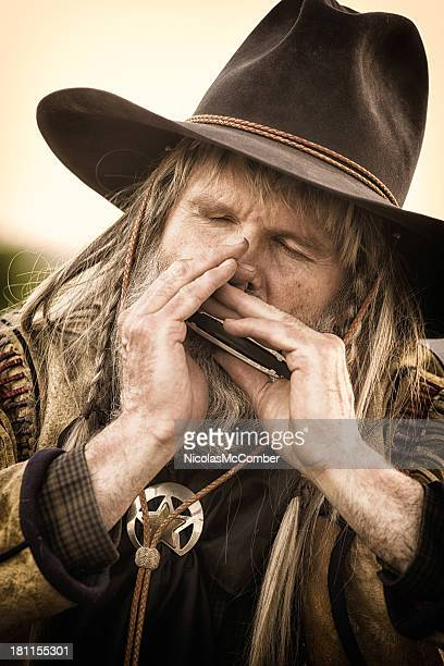 Old cowboy playing harmonica close-up