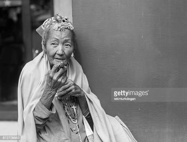 old cuban lady smoking cigar at street of havana cuba