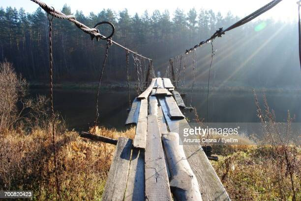 Old Damaged Wooden Bridge Over River Leading Towards Forest On Sunny Day