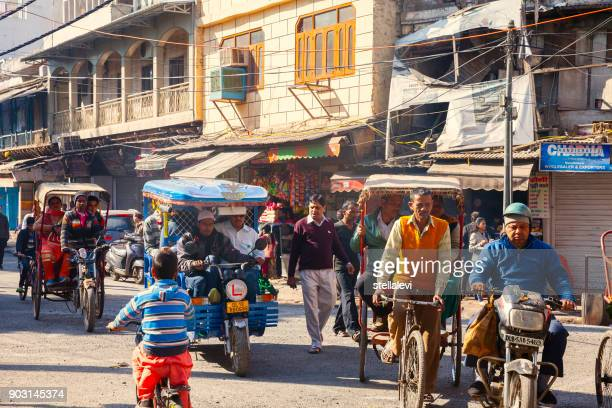 old delhi street with rickshaw drivers and pedastrians - old delhi stock photos and pictures
