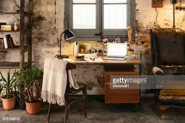 old desk with laptop in a loft - belongings stock photos and pictures