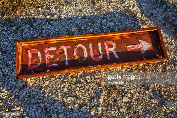 old detour sign on desert ground - wrong way stock pictures, royalty-free photos & images