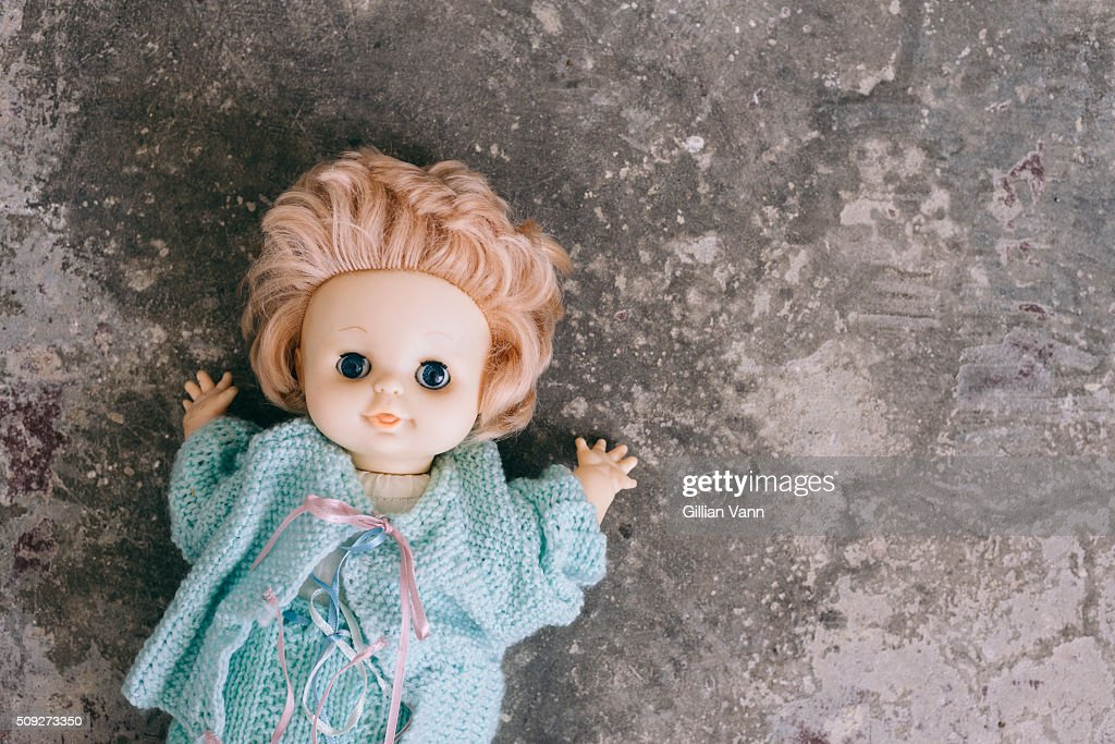 old doll abandoned on a concrete floor : Stock Photo