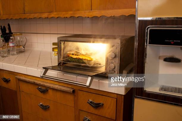 Old domestic kitchen with toaster oven on fire