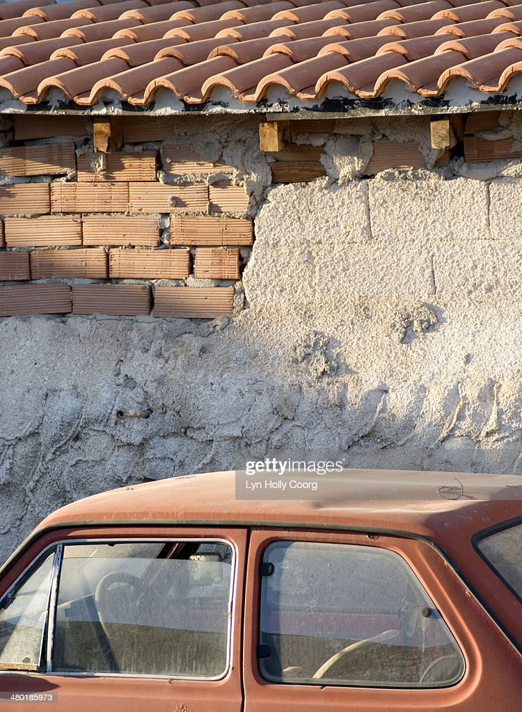 Old dusty orange car and orange wall and roof : Stock Photo