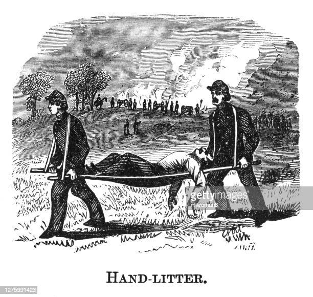 old engraved illustration of injured soldier is carried on a litter by companions - war stock pictures, royalty-free photos & images