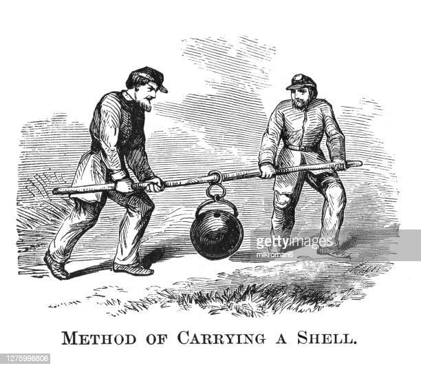 old engraved illustration of method of soldiers carrying the bomb - war stock pictures, royalty-free photos & images