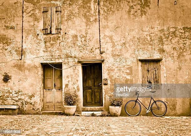 old facade with bicycle, sepia toned - sepiakleurig stockfoto's en -beelden