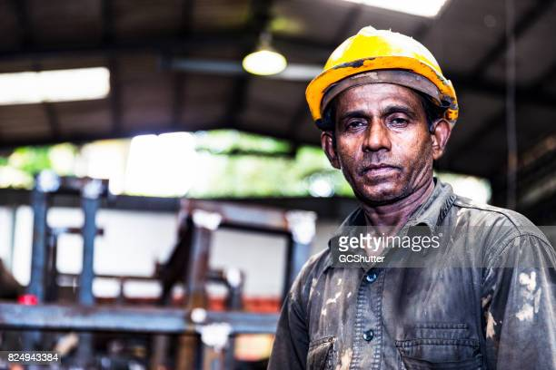 Old factory employee looking at the camera