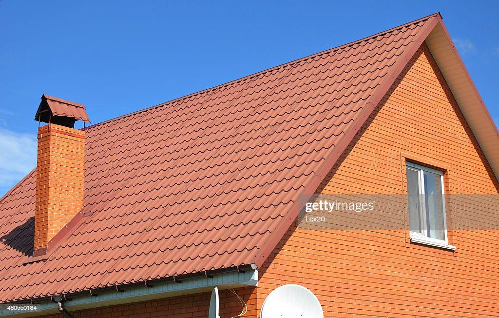 Velho desbotado vermelho Telha metálica e chaminé. Bad telhado. : Foto de stock
