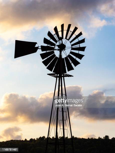 old farm style water pumping windmill at sunset. - traditional windmill stock photos and pictures