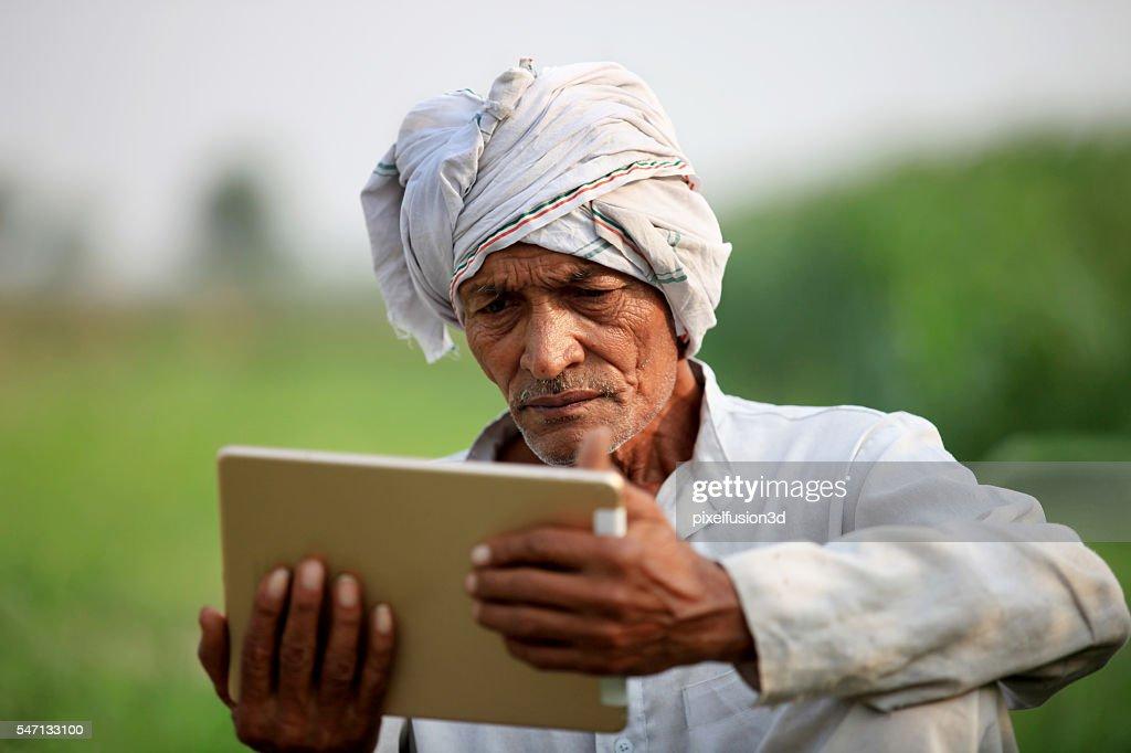 Old farmer holding digital tablet : Stock Photo