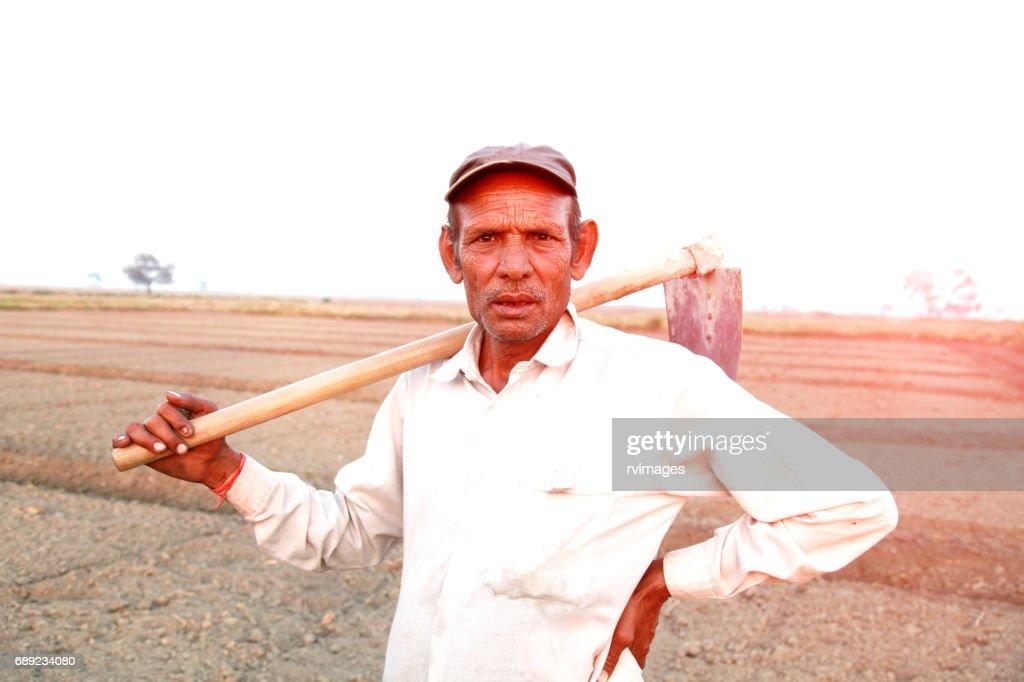 Old farmer holding garden hoe : Stock Photo