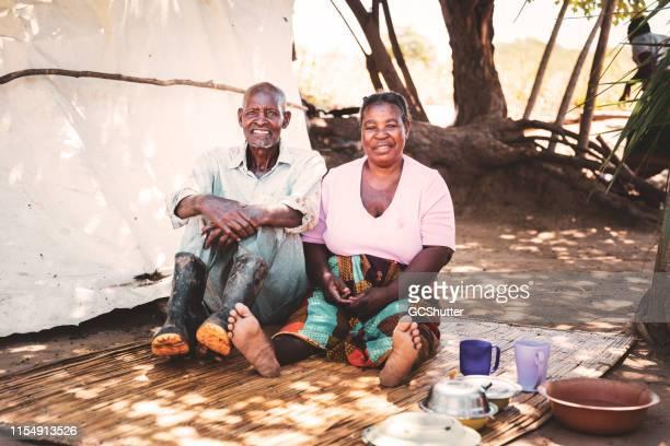 妻が小屋の近くのわらのマットの上に座っている古い農夫 - ザンビア ストックフォトと画像