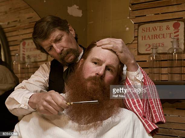 Old fashioned barber giving man a shave