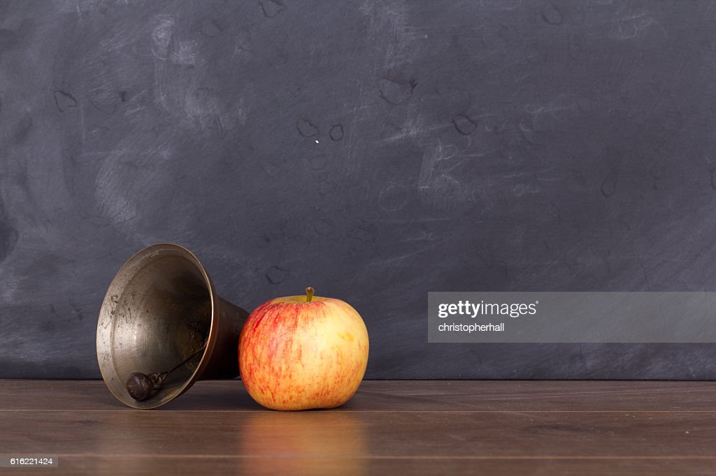 Old fashioned bell and apple against a blackboard : Stock Photo