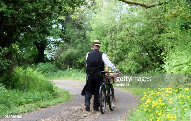 old fashioned delivery man from 1940's in rural setting - straw boater hat stock pictures, royalty-free photos & images