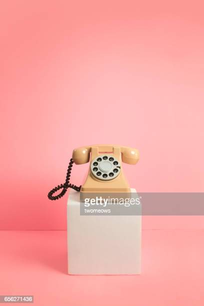 Old fashioned dial telephone on pink background.