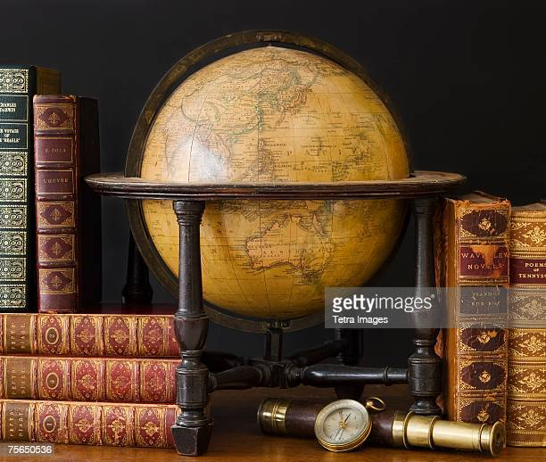 Old fashioned globe and books on table