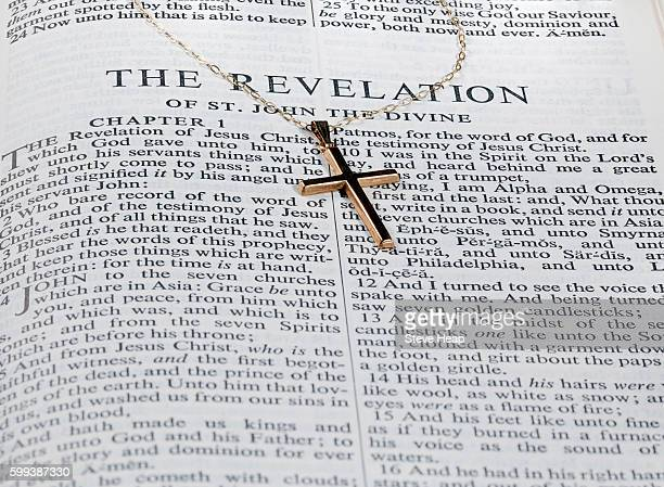 Old fashioned gold cross and chain laying on a page from the bible on the revelation