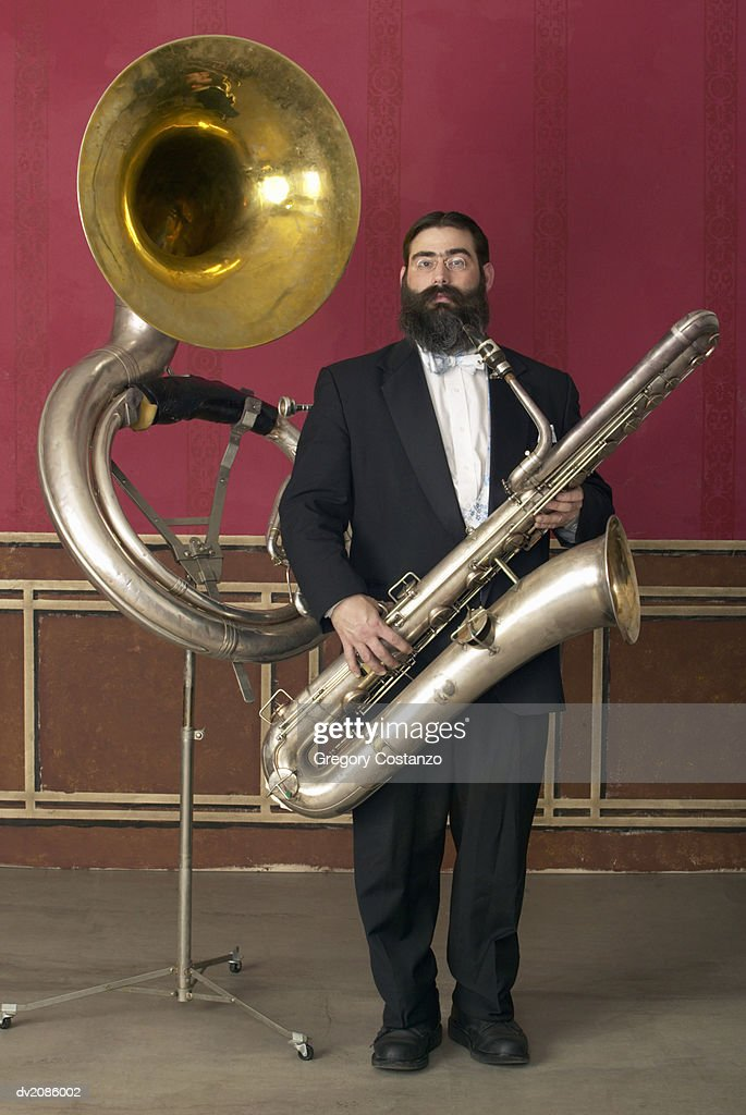 Old Fashioned Man in a Suit Holding a Large Saxophone, Standing Next to a Tuba on a Music Stand : Stock Photo