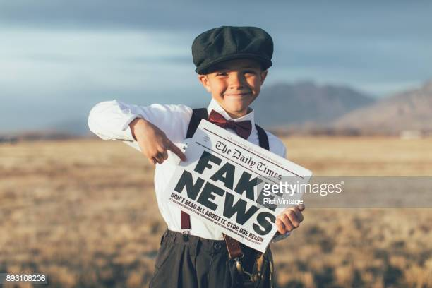 old fashioned news boy holding fake newspaper - news event stock pictures, royalty-free photos & images