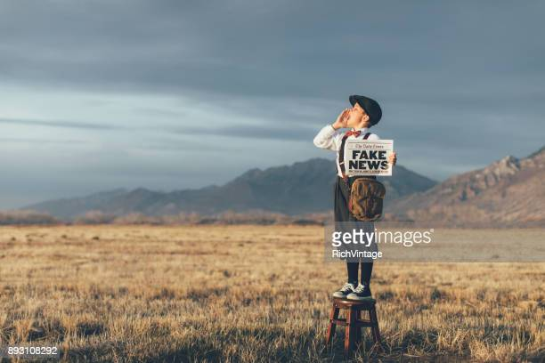 old fashioned news boy holding fake newspaper - plus fours stock photos and pictures