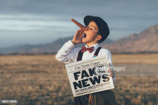 old fashioned pinocchio news boy holding fake newspaper - fake stock pictures, royalty-free photos & images