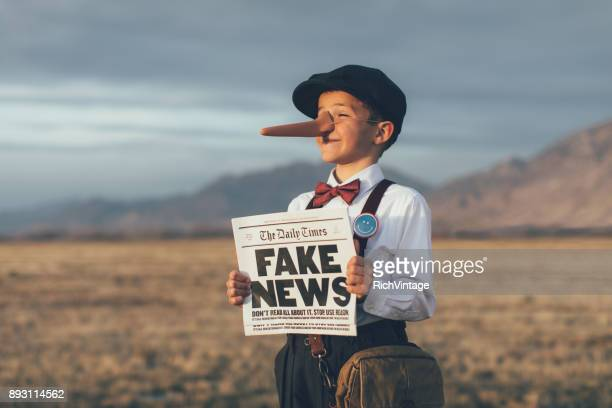 old fashioned pinocchio news boy holding fake newspaper - long nose stock photos and pictures