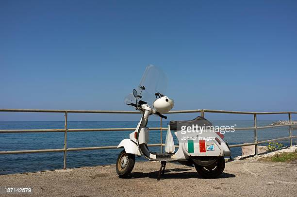 old fashioned scooter at seaside - moped stock photos and pictures