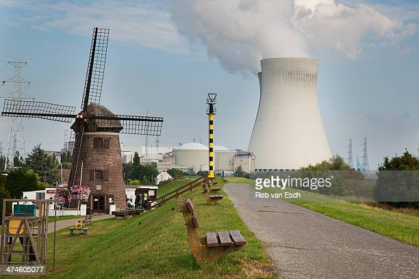 Old fashioned windmill standing next to a nuclear power plant in Doel, Antwerp, Belgium, symbolising old and new energy.